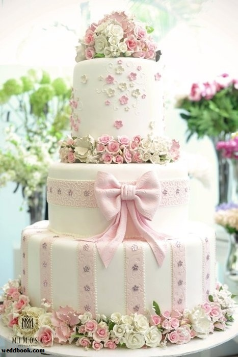 3 tier round cake with pink bow and flowers